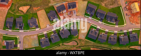 New construction upper middle class single family home neighborhood in America with empty lots - Stock Photo