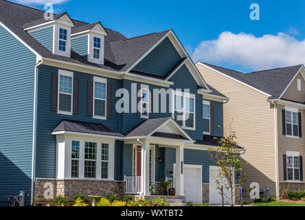 Colonial style sign family home with gable roof, dormer windows, white porch cornice on the room, eaves, grey and blue vinyl siding in the USA - Stock Photo