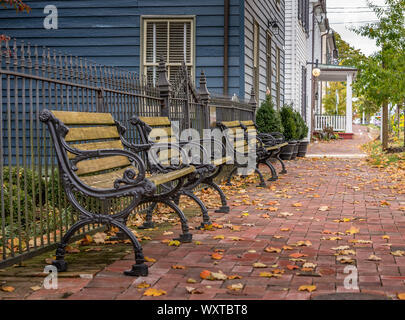 Wooden bench with iron frames on a colonial brick street in New Market Maryland with autumn leaves - Stock Photo
