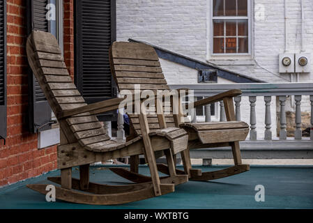 Wooden rocking chairs on a colonial porch somewhere in America - Stock Photo