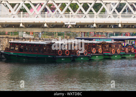 Singapore river cruise bum boats floating on water. These boats are for sightseeing purpose for tourists visiting Singapore. - Stock Photo