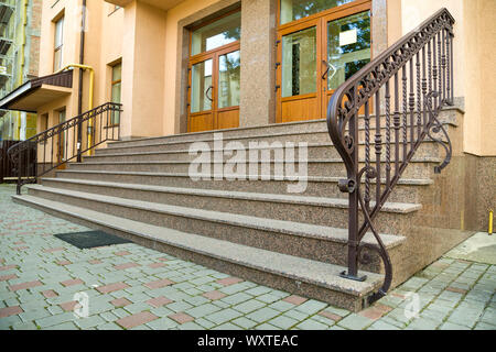 Detail of a house facade. New granite stairs with metal railings. - Stock Photo