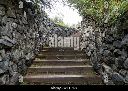 A long high staircase with wooden steps extending upward surrounded by stone walls in summer. Travel and mystical places. - Stock Photo