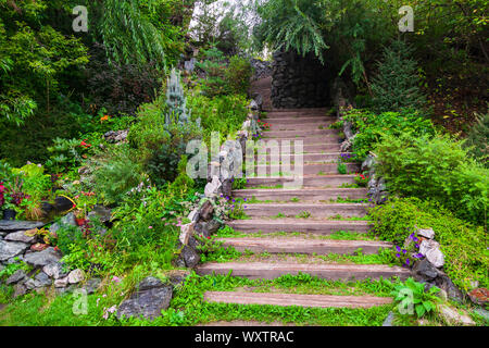A long high staircase with wooden steps extending upward surrounded by stones and green plants in the garden in summer. Travel and mystical places. - Stock Photo