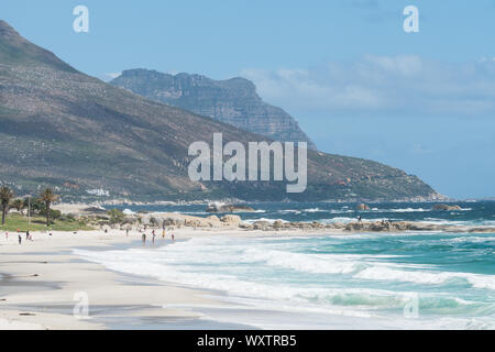 Camps Bay landscape and seascape of white sandy blue flag beach and turquoise water of the Atlantic ocean with beachgoers in Cape Town, South Africa - Stock Photo