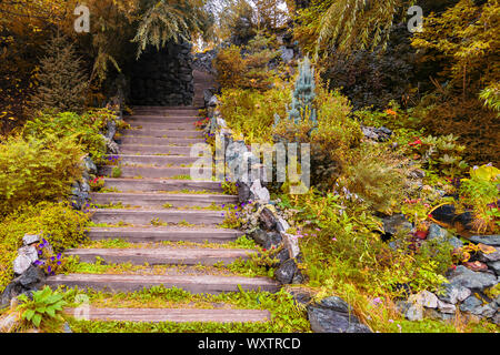 A long high staircase with wooden steps extending upward surrounded by stones and yellow plants in the garden in indian summer autumn. Travel and myst - Stock Photo