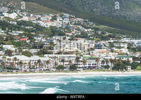 upmarket coastal residential suburb of Camps Bay in Cape Town and residences up against the mountain with the white sandy beach and turquoise ocean - Stock Photo