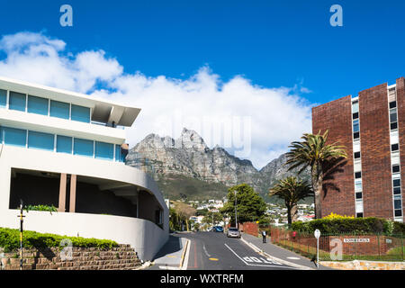 suburban street view of upmarket residential suburb of Cape Town,South Africa called Camps Bay and view of Table Mountain and buildings in Spring - Stock Photo