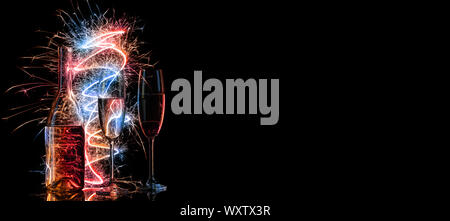 Bottle and two glasses of champagne in multi-colored sparklers on black background. Concept for celebrating Christmas, New Year and other celebrations - Stock Photo
