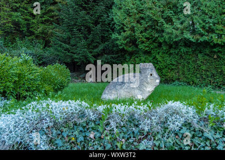 Sculpture of a stone rabbit on a lawn next to a bush in the city of Meix in front of Virton in Belgium - Stock Photo