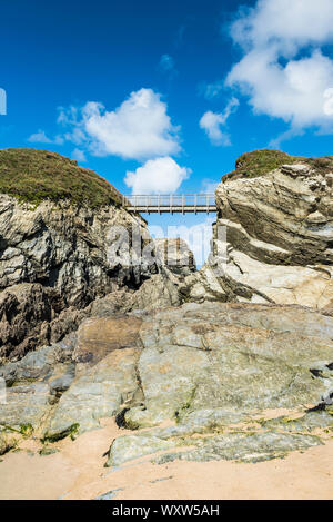 The footbridge connecting the mainland to Porth Island at Porth Beach in Newquay in Cornwall. - Stock Photo