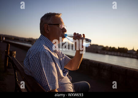 Outdoor portrait of senior man who is drinking water. - Stock Photo