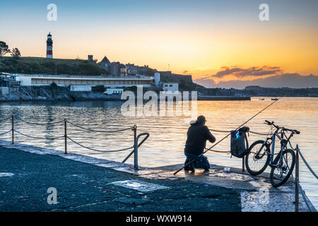 Plymouth, Devon, England. Wednesday 18th September 2019. UK Weather. After a cold night, in the first light of dawn an angler waits for a bite as the sky glows pink over Smeatons Tower on The Hoe and the harbour in Plymouth, Devon, South West England . Credit: Terry Mathews/Alamy Live News - Stock Photo