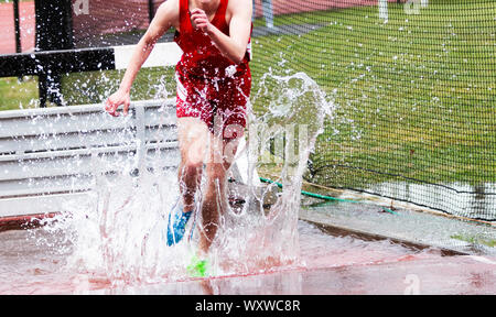 A high school boy landing in the water during a steeplechase race and splashing water everywhere. - Stock Photo