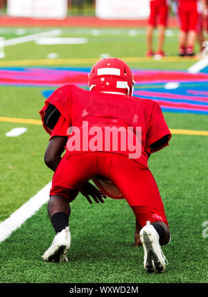 A high school football player at practice in a three point stance on a green turf field in all red clothing, - Stock Photo