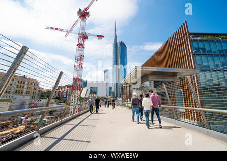Milan, Italy: pedestrian bridge in the Porta Nuova Varesine district with the construction site cranes for the new skyscraper called Vertical Nest - Stock Photo
