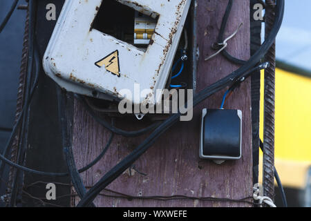 Self made rusty electric box. Energized electrical equipment. Dangerous, high voltage! - Stock Photo