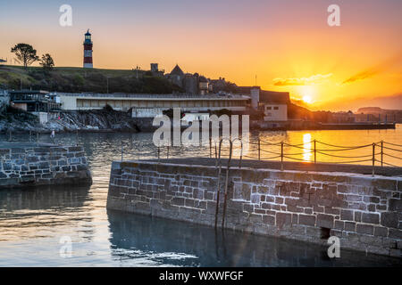 Plymouth, Devon, England. Wednesday 18th September 2019. UK Weather. After a cold night, the first rays of sunshine break through the clouds as the sky glows pink over Smeatons Tower on The Hoe and the harbour in Plymouth, Devon, South West England . Credit: Terry Mathews/Alamy Live News - Stock Photo