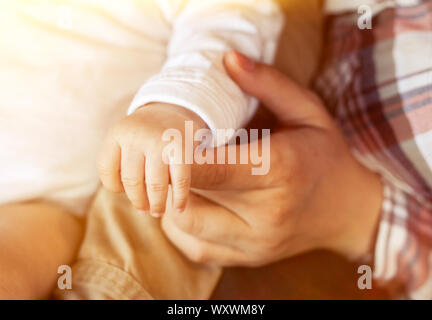 Cute little baby's hand holding mother's finger close up picture at home. Family, childhood concept. - Stock Photo