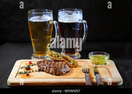 Steak and beer. Grilled meat - Cold Beer. Delicious steak. - Stock Photo
