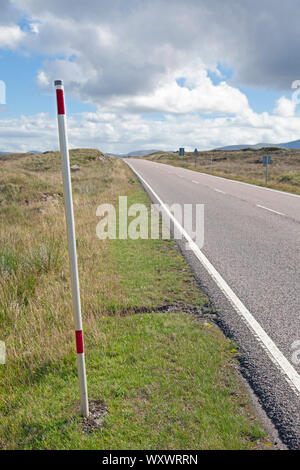 UK, Scotland, Argyll, Road through Glen Coe in the Scottish Highlands with pole to guide snow ploughs - Stock Photo