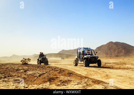 Merzouga, Morocco - Feb 24, 2016: convoy of off-road vehicles (RZR, Quad and motorbikes) in Morocco desert near Merzouga. Merzouga is famous for its d - Stock Photo
