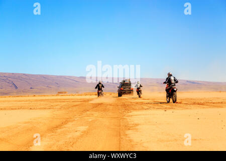 Merzouga, Morocco - Feb 22 2016: convoy of off-road vehicles (4x4 and motorbikes) in Morocco desert near Merzouga. Merzouga is famous for its dunes, t - Stock Photo