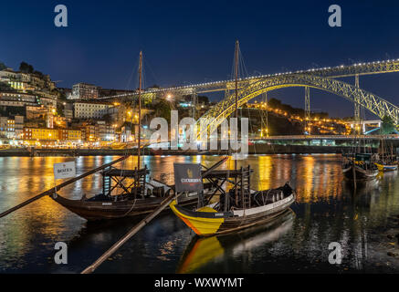 Rabelo boats used to transport port in Porto in Portugal with a panorama of the skyline of the old town at night with lights reflecting in the river - Stock Photo