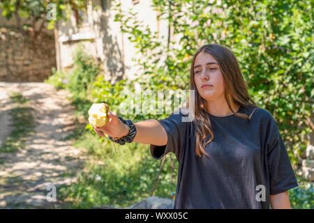 Cukuroren, Bilecik / Turkey -September 08 2019: Portrait of a girl holding at a half eaten apple and green tree in background - Stock Photo