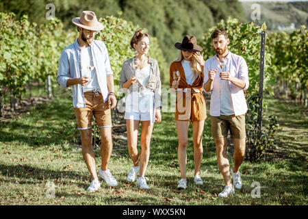 Group of young friends dressed casually having fun together, walking with wine glasses on the vineyard on a sunny summer morning - Stock Photo
