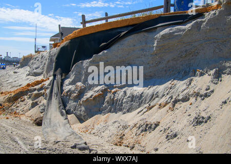 Erosion of the sand of the beach with destruction of a asphalt path after a hurricane and storm. - Stock Photo