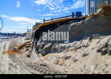 Atlantic City, New Jersey - September 9, 2019: Erosion of the sand of the beach with destruction of a asphalt path. The Steel Pier with its ferris whe - Stock Photo