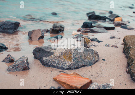 pebbles on a sandy shore in clear water. The silky waves of a blue lake hit the stones. Natural background. - Stock Photo