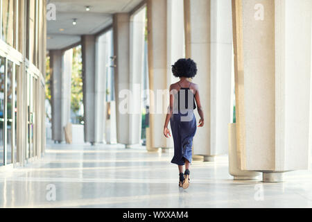 A young fashionable Afro-American woman walking away from the camera - Stock Photo