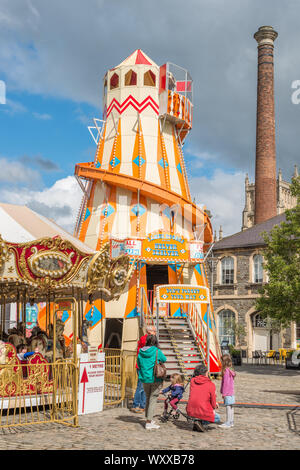 A helter skelter fairground ride on Anchor square in Bristol city centre with Rowes Leadworks chimney to the rear, Avon, England, UK. - Stock Photo