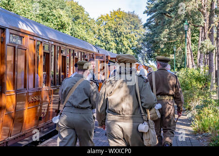 Group of people dressed as 1940s soldiers walking up the railway platform in Holt to board a rail carriage during the annual forties weekend held in H - Stock Photo
