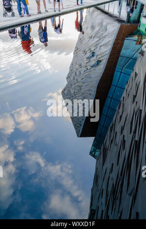 Belfast, Co Down/Northern Ireland: Reflections of people looking into the water around the Titanic Building in Belfast. - Stock Photo