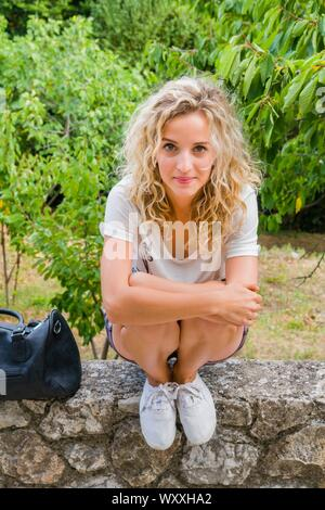 Cute blonde haired teen girl next door is squatting on stone wall waiting wait looking at camera eyeshot squatter - Stock Photo