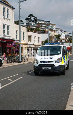 A police van with blues and two's operating passes through the main street at St Aubin, Jersey, Channel Islands - Stock Photo