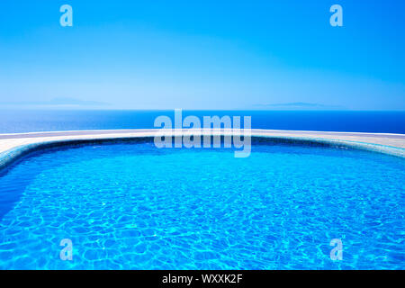 Swimming pool with a view of the sea, La Palma, Canary Islands, Spain, Europe. Island Tenerife and Island La Gomera in the background. - Stock Photo