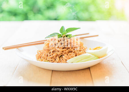 fried noodles with chilli on wood table - Stock Photo