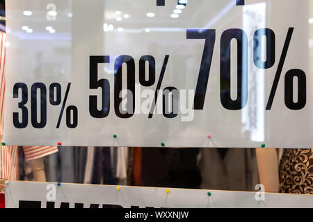 Showcase of clothing store in season of discounts, banner with inscriptions of discount sizes, 30, 50, 70 percent. Concept shopping, discounts, black - Stock Photo