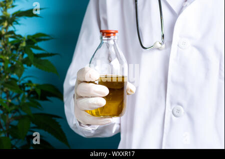 Scientist holding cannabis oil close up, alternative medicine abstract - Stock Photo