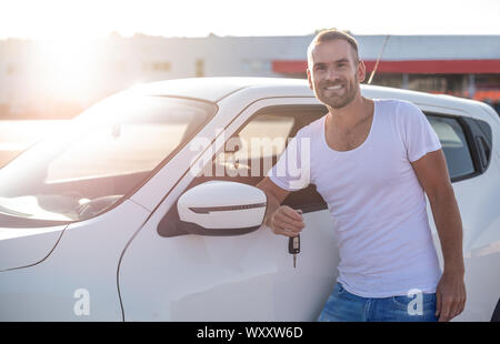 A male driver stands near a car with a key in his hand and smiles. - Stock Photo