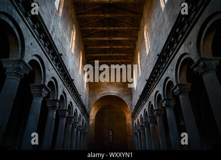 The interior with stone columns and Corinthian capitals and the ceiling with wooden beams of an ancient church or medieval cathedral, with colonnade - Stock Photo