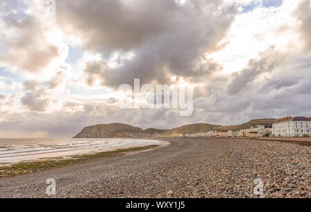 A view of Llandudno's curving shoreline with dramatic clouds.  The Little Orme headland is in the distance and sun rays illuminate a field. - Stock Photo