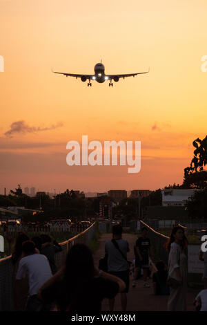 Spectators watch and take photos from 'Airplane Alley' as an Airbus A321 makes its approach to Songshan Airport, Taipei at dusk - Stock Photo