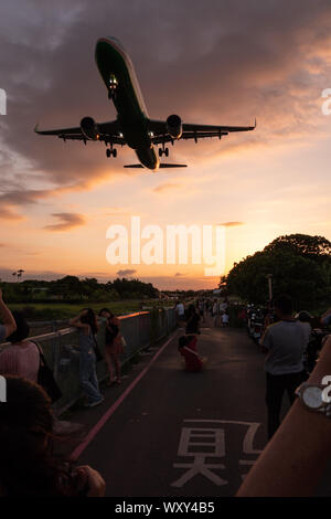 Spectators watch and take photos from 'Airplane Alley' as an Airbus A321 low over their heads on approach to Songshan Airport, Taipei - Stock Photo