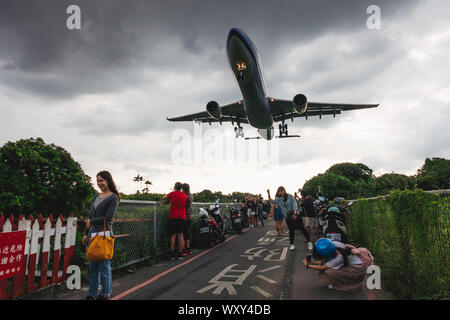 Sunset at 'Airplane Alley' - people pose for photos as an Airbus A330-300 flies low over their heads on approach to Songshan Airport, Taipei - Stock Photo