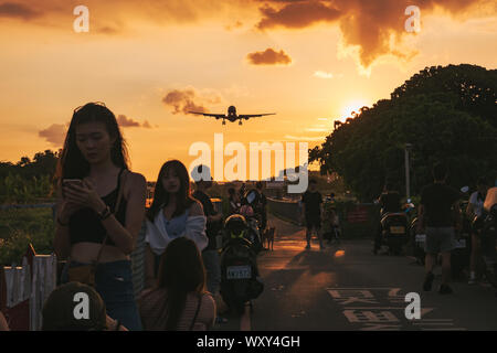 Spectators prepare themselves for a photo as an Airbus A330 approaches at sunset to land at Taipei Songshan Airport, Taiwan